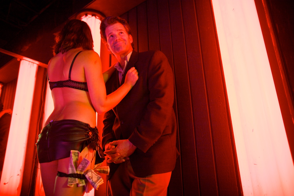 Author Andre Dubus, right, poses with an exotic dancer for a portrait inside a strip club that is similar to the one in his novel The Garden of Last Days.