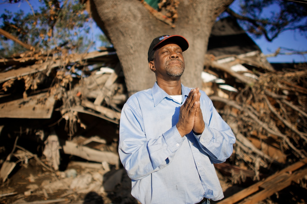 Katrina survivor Robert Green says a prayer in front of the debris of what used to be his house in the lower 9th Ward. Green said that his house hit against the large oak tree when it floated off of its foundation during the storm. In the process of evacuating his family from the house to the more stable tree he lost the grip of his mother and granddaughter who were swept away in the storm water and died.