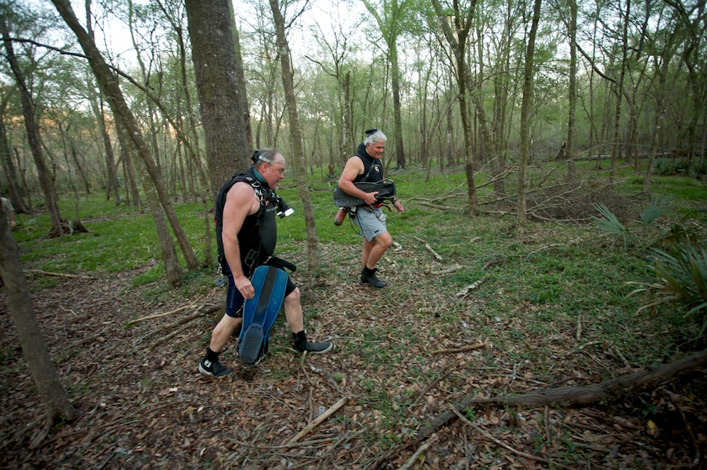 Springs guide and SCUBA diver Wes Skiles, left, and Tom Morris tramp through muddy woods in full scuba gear in search of a fissure or spring opening.
