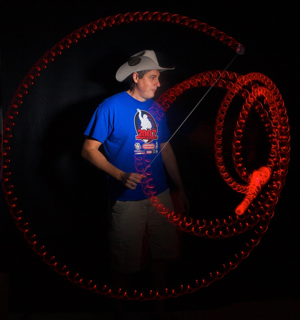 Lucky Meisenheimer poses for a portrait while demonstrating a trick with a light-up yo-yo during a time-lapse photo during a welcoming party for yo-yo competitors.