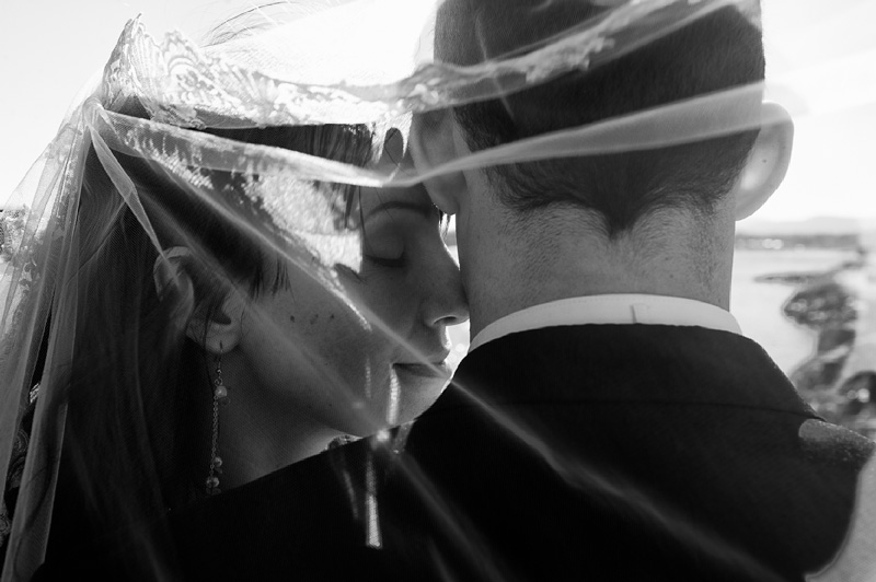 In a black and white photo a bride presses her nose to the groom.  Both are covered in her veil.