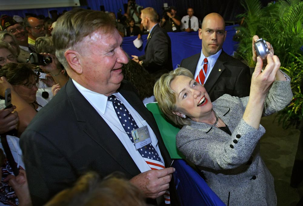 Senator Hillary Clinton of New York, right, held up the camera of VFW member Lud Bezemek, left, along the greeting line for Clinton after she spoke at the VFW 108th National Convention at Bartle Hall.