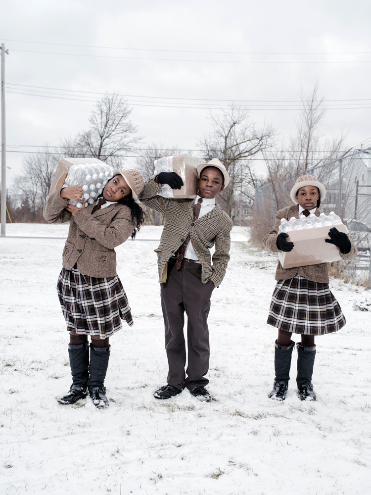 Antonio Abram(13), with his sisters, Julie Abram(12), and India Abram(12), collect their daily allowance of bottled water from Firhouse #3, Martin Luther King Avenue, Flint, Michigan, January 27, 2016.