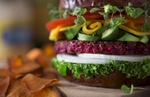 A low angle view of a beet patty hero sandwich made with raw white onion and tomato slices, rolled mango slices substitue for cheese and avacado chunks stacked high on a pretzel bun. Lettuce and bean sprouts finish this entree which sits on a distressed wood cutting board and is served with roasted sweet potato rounds. Dramatically lit from the left, the background is muted and out of focus exhibiting strong bokeh effect cropped in a landscape orientation.