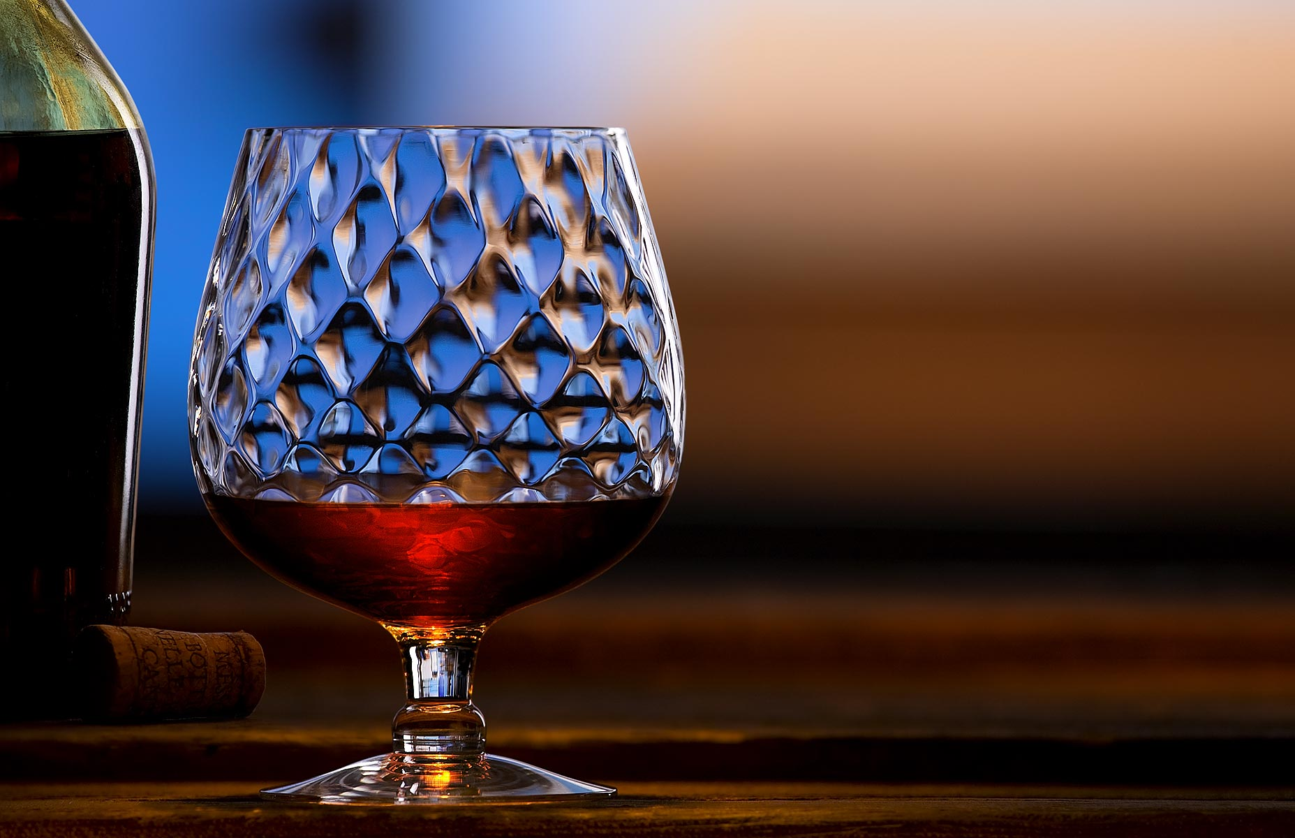 Camera is at 0º and the lighting is frome back and right of frame in this landscape aspect product and beverage image. The single snifter is partially filled with a hint of the bottle on the left side and a cork stopper is placed between all composed on a weathered wood bar top. The soft focus background exhibits a desireable bokeh effect in its rich brown and blue hues.