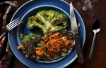 Served on a rich blue rimmed plate, this center sliced green cauliflower has been roasted and placed in a shallow pool of basil pesto sauce. The foreground side dishes include thinly sliced roasted sweet potatos, sauteed mushrooms and garlic slices with carmalized red onions . The landscape orientation, straight down camera angle and dramatic lighting create a delicious addition to this visually intense composition. A completely vegetarian and gluten free entree which tastes as wonderful as it looks.