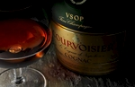 A bottle of VSOP Courvoisier dominates the horizontal frame with a partially filled snifter. The camera angle is at 45º and the subjests sit tightly on a rough hewn stone bar top. The feeling is moody and the soft light originates on the left side highlighting the glasss and label. A reddish glow also illuminates the lower label from light passing through the fluid.