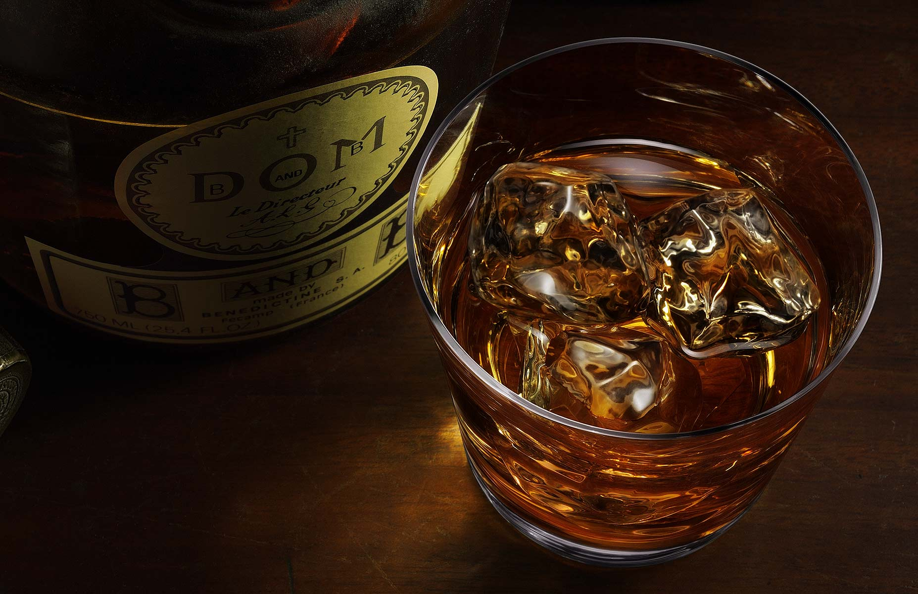 The camera aspect is at 60º in this brooding product photograph of a Dom B & B bottle with a lowball glass half filled with ice and Irish whiskey. The bottle stopper is mysteriously in the shadows left of the centered bottle with the ice and whiskey glass on the right. A soft focus tankard rests subtly in the upper right corner and the subjects are comfortably composed on a rustic wood surface.