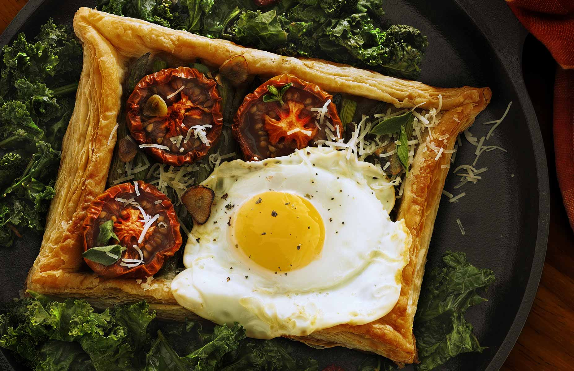 Fried Egg En Croute is an entree made with Phyllo dough shaped into a rectangular shell photographed from above. It is filled with asparagus, roasted tomatos, sauteed garlic, parmesan cheese then baked with spices and herbs. The delectable treat is finished with a fried egg and served on a bed of kale leaves all resting on a cast iron grill pan on dark wood. The image is in a landscape orientation and softly back lit.
