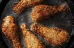 A southern classic of freshly battered chicken drumsticks frying in lard. The composition is tightly cropped and seen from above. The subject resides in a cast iron fry pan on a black stove. There are five pieces of chicken and the slow shutter speed creates a wonderfully turbulent pool of 350º fat. Our lighting is from the left and the sculptural quality contrasts with the motion of the bubbling oil. This image is predominantly black and golden brown in a landscape orientation.