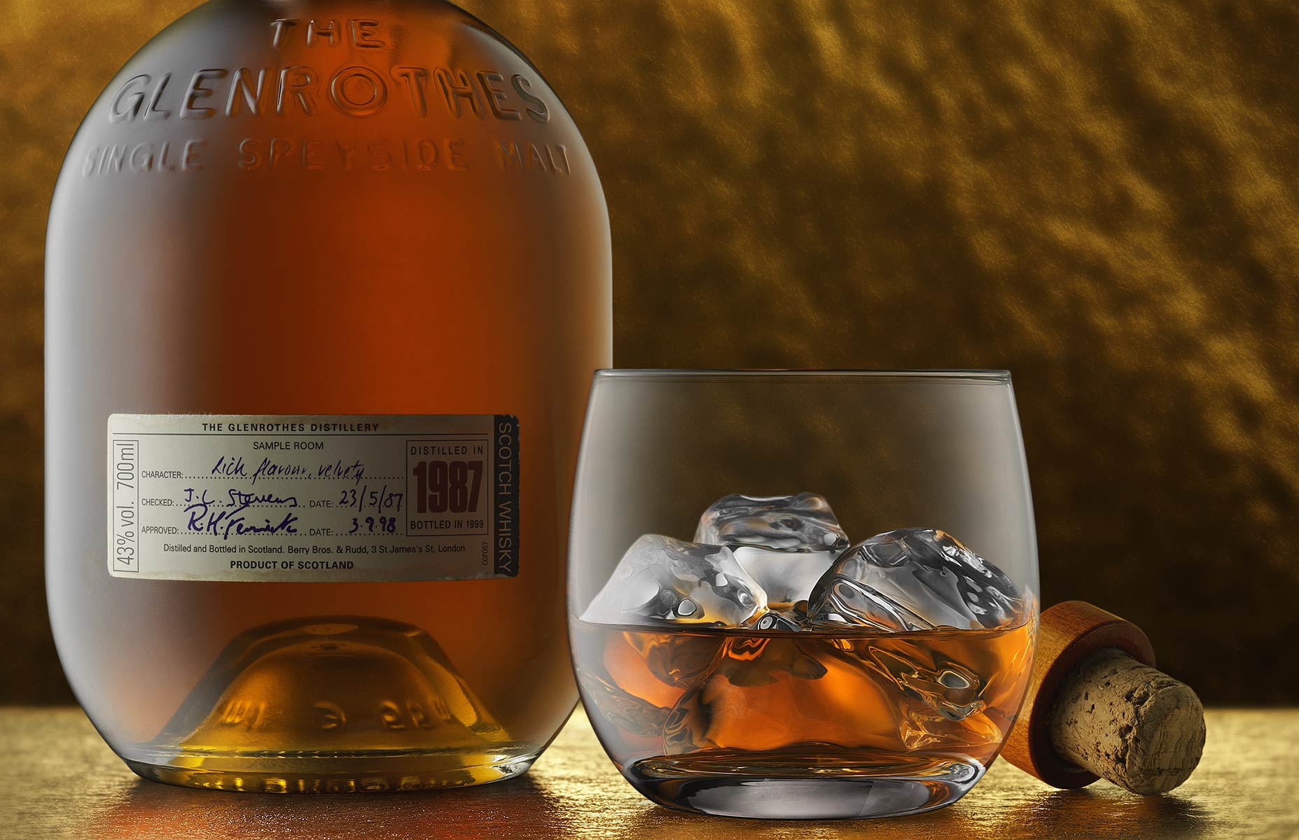 Shot with the camera angle at 0º to the bottle and cropped in a horizontal aspect. The cork bottle stopper is slightly obsured by a lowball glass half filled with ice and Scotch whiskey. The composition is on a pebbly and slightly reflective gold surface and in front of the textural gold back wall. The light is soft and from two directions, the main light is softly from the left side and a top light creates an interesting glow to the gold surface highlighting the whiskey and and adding depth to the subject's reflections in this still life.
