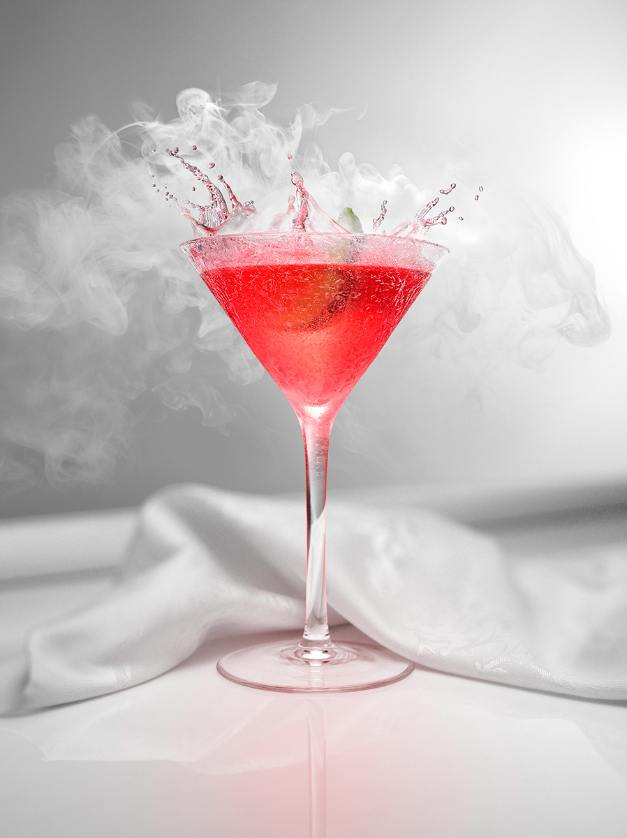 The camera is dead on (zeroed out) to this portrait aspect composition. Vaporization from the liquid nitrogen creates dancing white plumes as the lime wedge drops into this drink splashing the beautifully saturated red fluid made with lime juice, Cointreau, vodka and cranberry juice. Served in a traditional frozen martini glass sitting on an all white reflective bar top with gorgeous light from the right. A fine white linen napkin cradles the back of the glass stem.