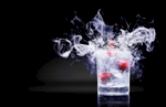 A single descending cherry drops into this delicious cauldron of vaporous liquid nitrogen and freezing vodka with Maraschino cherry garnish, creating splashes above the glass rim and in the liquid nitrogen vapor. This cocktail is served in an ice packed frozen lowball glass. The low camera angle creates additional drama to the soft, back and side lighting. The black background has a highly reflective quality which the glass reflects perfectly on.