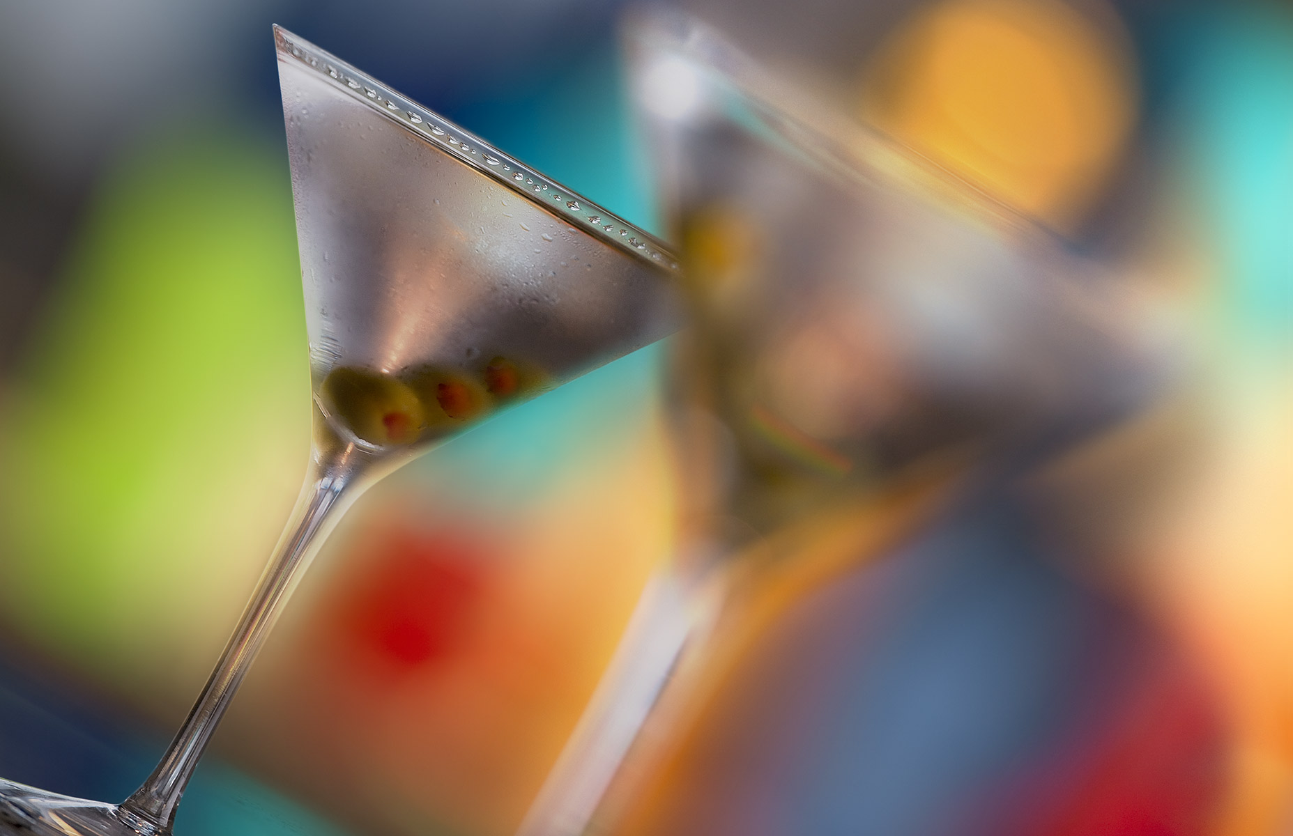 The camera placement is dead-on to the naturally sweating martini glass and cocktail which also has three pimento stuffed olives on the skewer. Served on a reflective black bar top the multiple, saturated out of focus colors exhibit a desireable bokeh effect and are reflected in the surface. The extremely out of focus second glass dominates the center and right of frame. The subjects are tilted towards 30º in this horizontally cropped photograph.