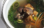 This image of Miso Soup is photographed at a 45º angle and is cropped tightly in a landscape orientation. The dish incorporates leeks, carrots, seaweed and shitake mushrooms in a miso broth with sprinkles of sesame seeds in a white bowl. The back and side lighting technique creates depth in the broth and a sculptural effect to the mushrooms.