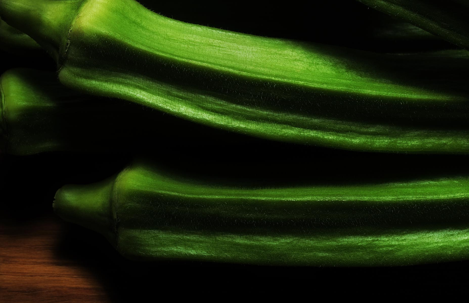 Extreme close up of just picked okra on a wood background. The camera angle is at 45º and the image is cropped in a landscape orientation. The late day light accentuates the highly saturated green of the okra in a very dramatic fashion.
