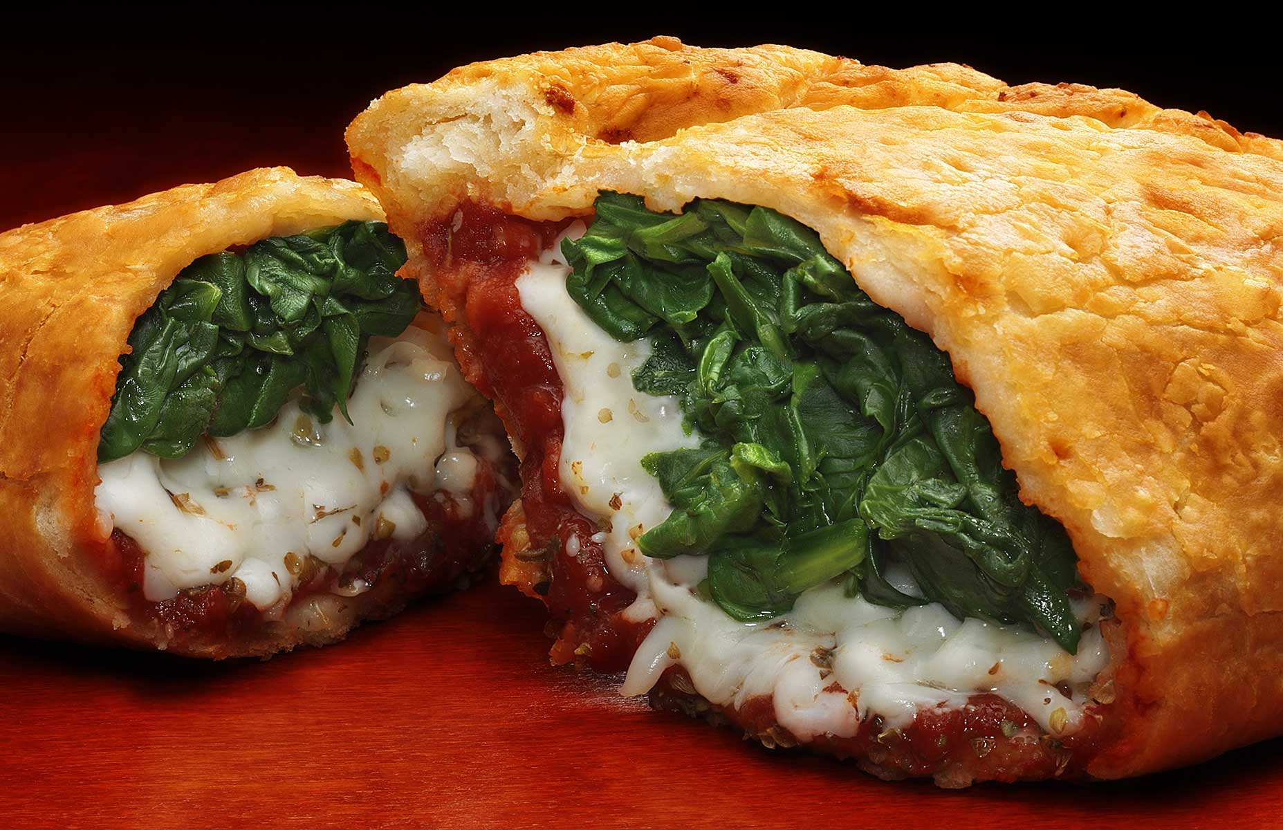 The low camera angle is directed at the opening of this cut Italian staple and gracefully stacked spinach style Calzone. It rests easily on a rich wood surface with the fresh marinara sauce and spinach layered with mozzarella in a crisp dough. This shot is in landscape orientation and is softly lit from back and above with additional light for the interior of the subject. The rich green of spinach, white of mozzarella and rich red of sauce are beautifully framed by the yellows and browns of the freshly baked crust all on a reddish wood surface.