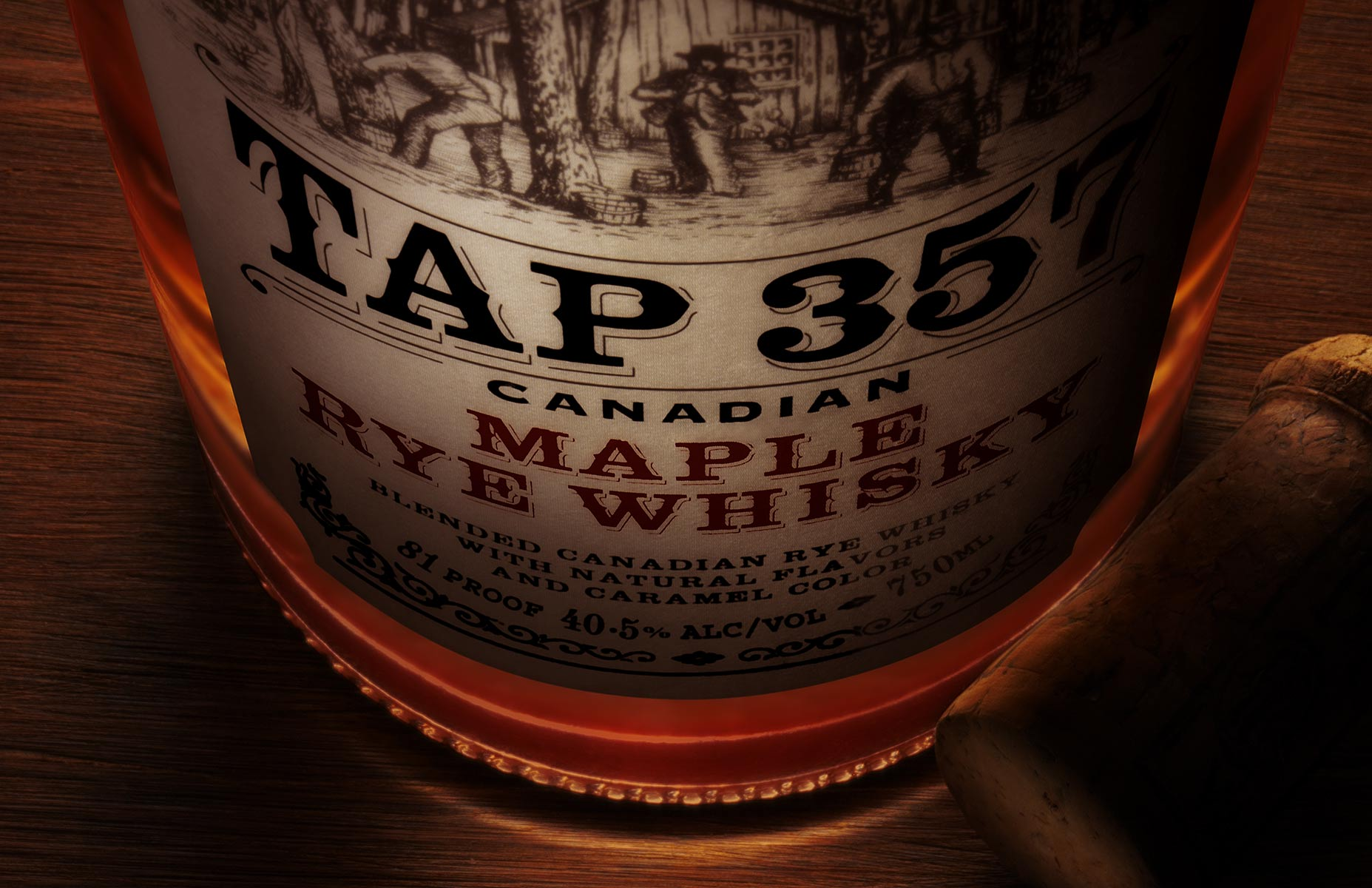 Product image exhibiting forced perspective dominates the visual appeal of the still life. The lighting is focused on the label of the bottle with an internal glow from the interior fluid. A cork rests to the right of the maple infused rye whiskey bottle and has a rim light effect. The subject is in sharp focus top to bottom and all sit on a rough hewn wood plane. The image is cropped in a landscape format.