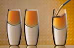 Three shots, the two on the left are already full with an aperitif pouring into the glass on the right side of frame. The background exhibits beautiful bokeh effects in the predominantly orange hue. The glasses are composed on a slightly reflective white with black and grey veined marble surface. The image is cropped horizontally and the camera is dead-on to the subject.