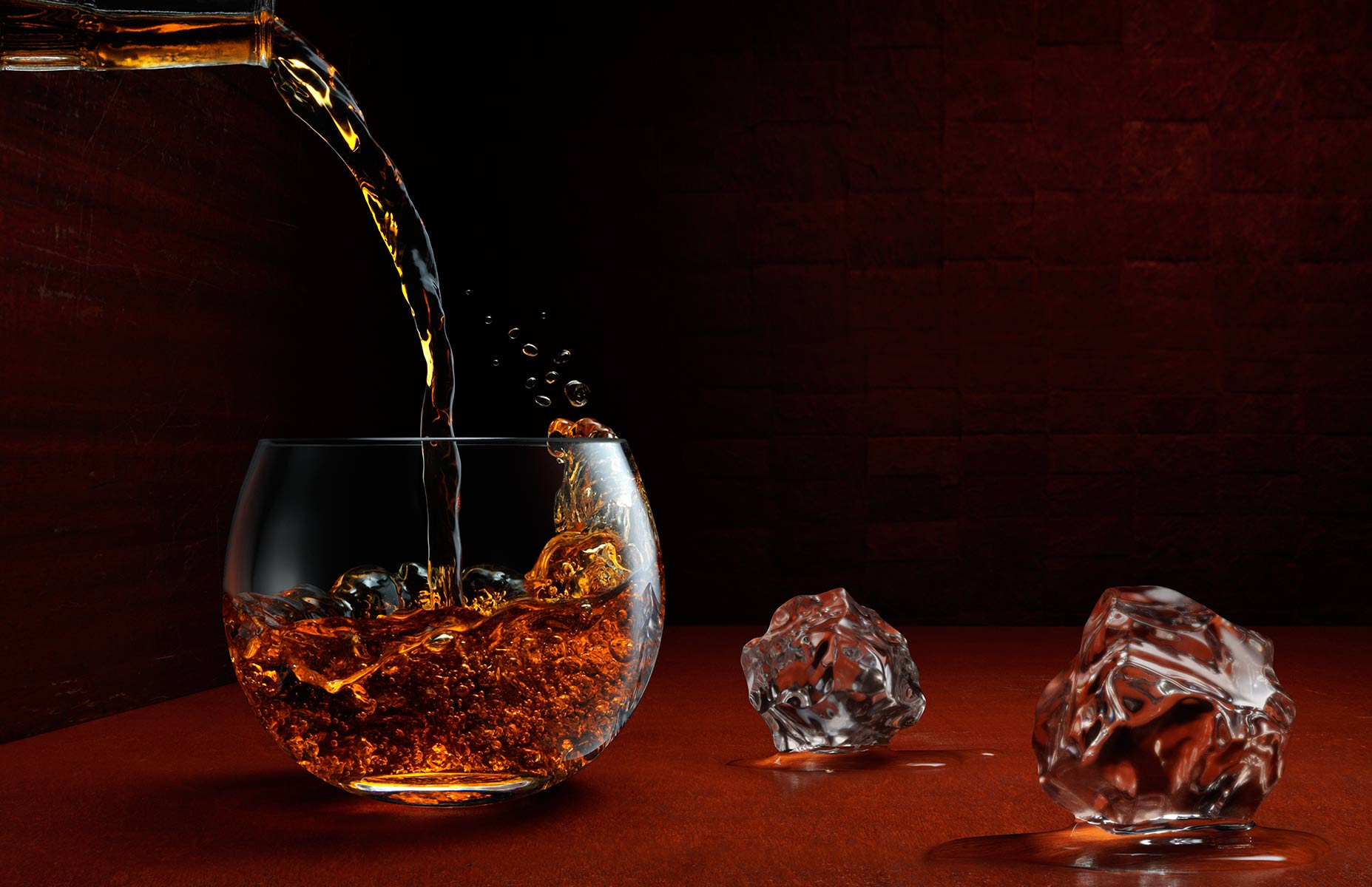Whiskey pouring from a bottle into a round lowball glass on a mahogany wood surface which fades to black with liquid splashing about. This example of high speed photography exhibits incredible detail while two ice cubes melt on the surface. This picture is in landscape orientation with a low angle of view and strong light source from the right.