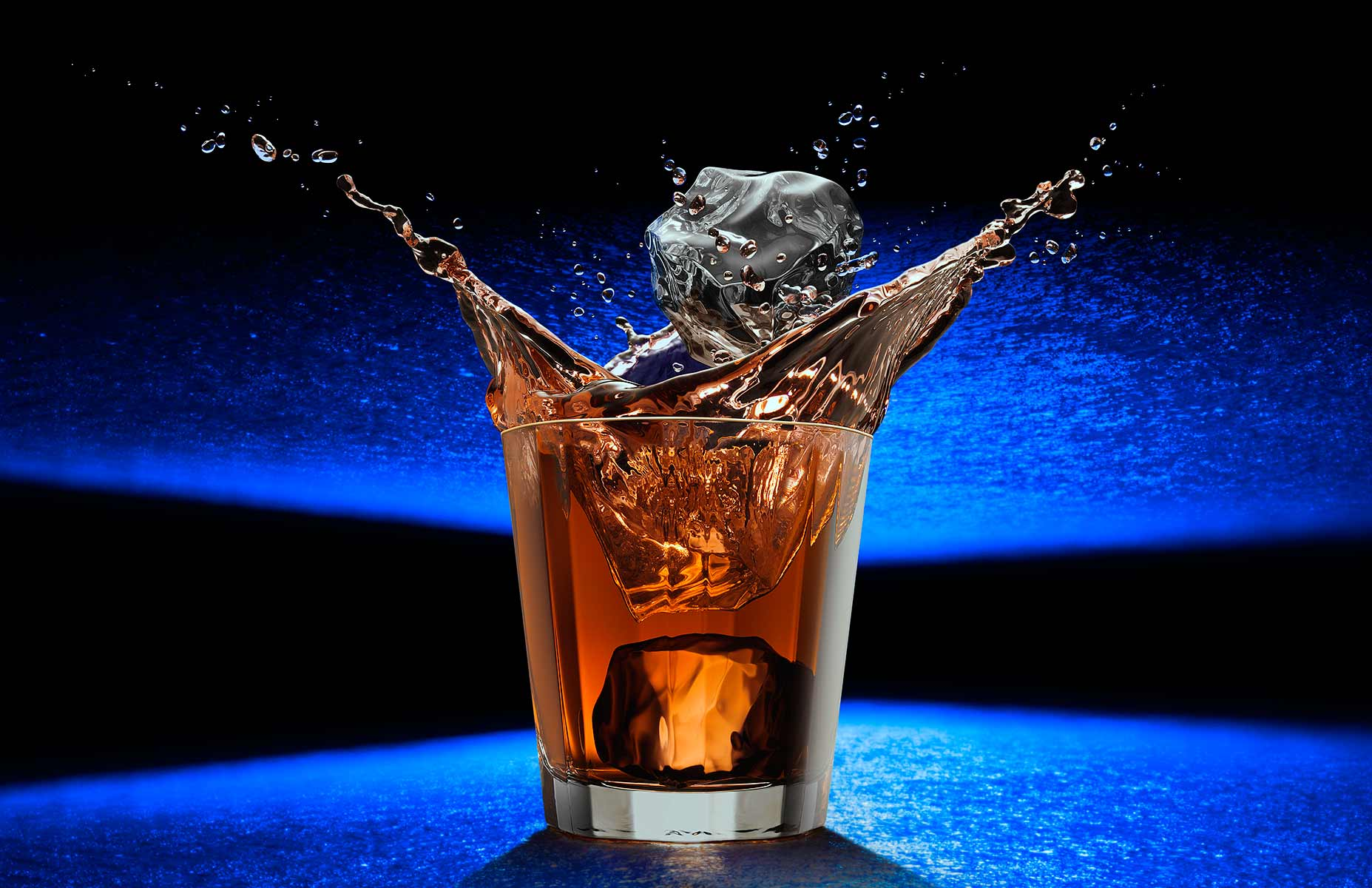 Dropping ice cubes suddenly hit the whiskey in a 12 sided polygon cocktail glass and creates a crown of splashing fluid. Photographed on a futurisic pebbly blue reflective surface in a landscape orientation. An example of high speed photography perfectly capturing and {quote}freezing the motion{quote} of the splashing fluid and descending ice cubes.