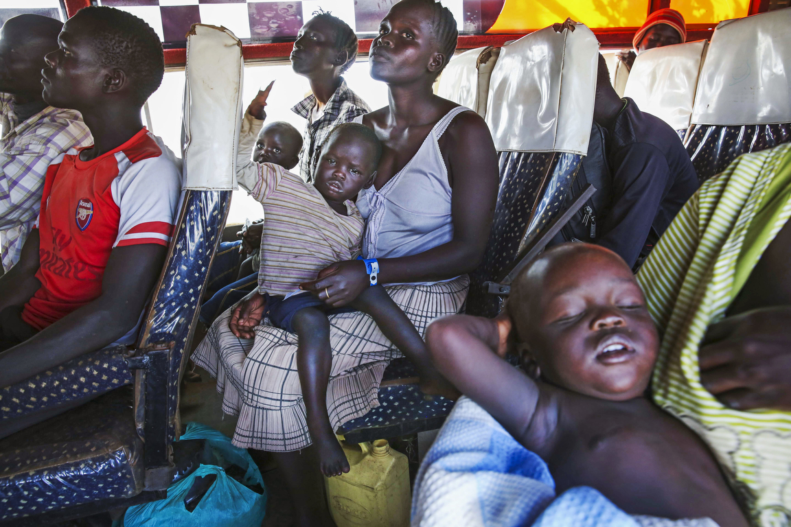 South Sudanese refugees wait for their intake cards while arriving on a transit bus to the reception center at the Imvepi Refugee camp on Friday, 23 June, 2017 in Northern Uganda.  The refugee crisis in East Africa his reached historic levels with Uganda hosting now more than 1.2 million refugees, Close to 1 million of which are from South Sudan.
