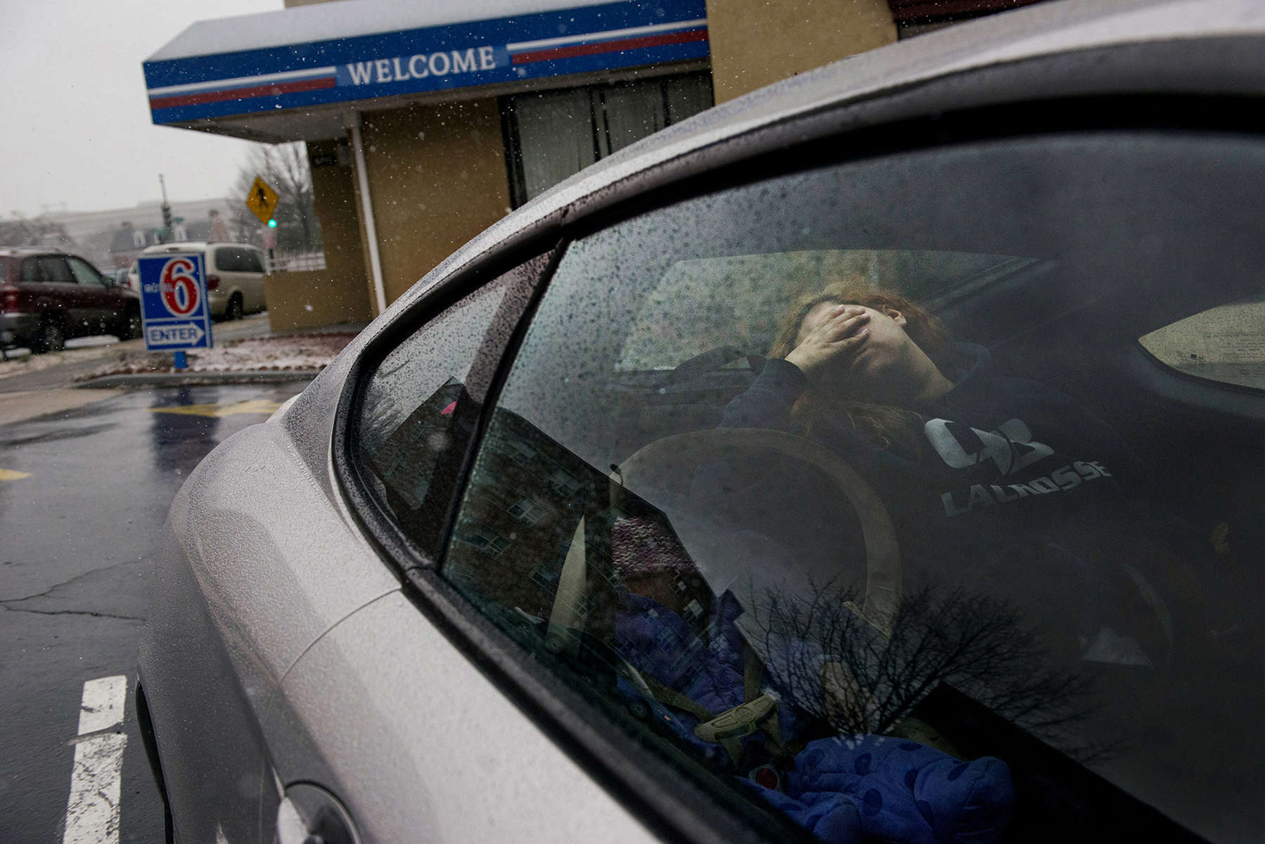 WASHINGTON, DC - JANUARY 21:   Melissa Morales rests in the back of the car while waiting to hear if her family would be given emergency shelter at the Motel 6 in place of DC family shelters on Tuesday, January 21, 2014 in Washington, D.C. Morales and her family were among the dozens of families lined up at the city's homeless intake center Monday seeking shelter for the night from the accumulating snow and freezing weather.  (Photo by Amanda Voisard/For the Washington Post)
