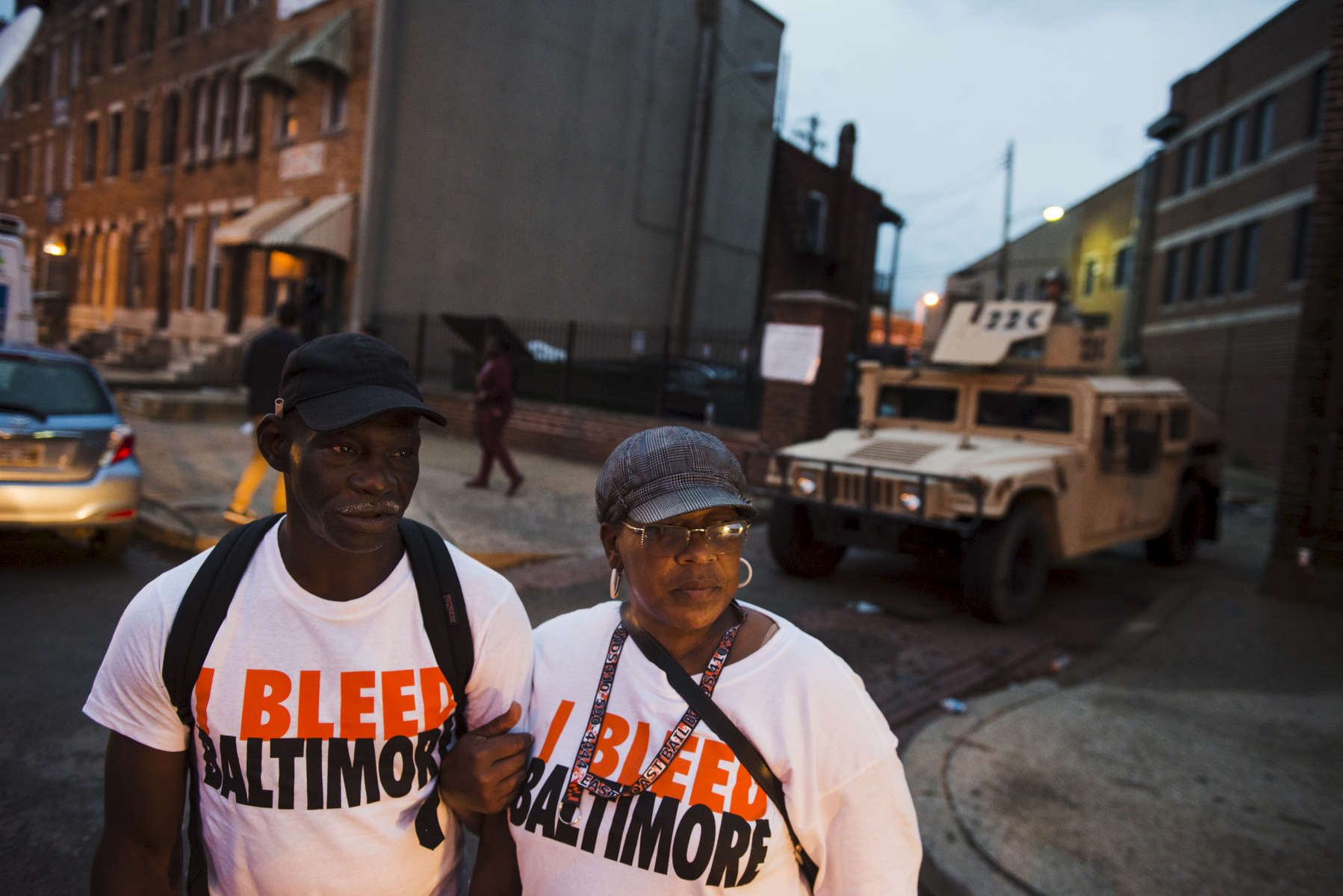 BALTIMORE, MD- APRIL 30:  Warren Morris, 53, and his cousin,Tracey Thompson, 50, wear \{quote}I Bleed Baltimore,\{quote} t-shirts made and distributed by local resident, Tony Daya, not pictured, while walking across at North Ave near Pennsylvania Avenue on Thursday, April 30, 2015 in Baltimore, MD.  Daya said he made the T-shirts for his friends and family but wanted to give them to the community as well, passing out over 20 cases of 150 shirts.  (Photo by Amanda Voisard/For the Washington Post)