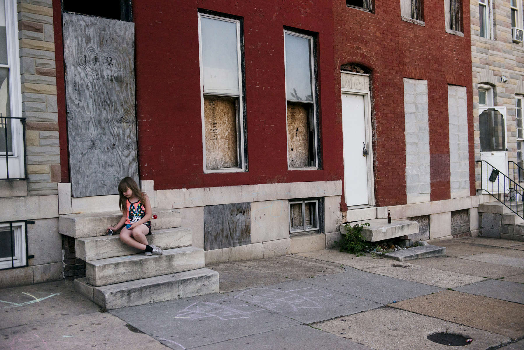 BALTIMORE, MD-  MAY 10:  Emily Painter, 7, plays in front of vacant row houses next to her home in the West side of Baltimore on Sunday, May 10, 2015 in Baltimore, MD. (Photo by Amanda Voisard/For the Washington Post)