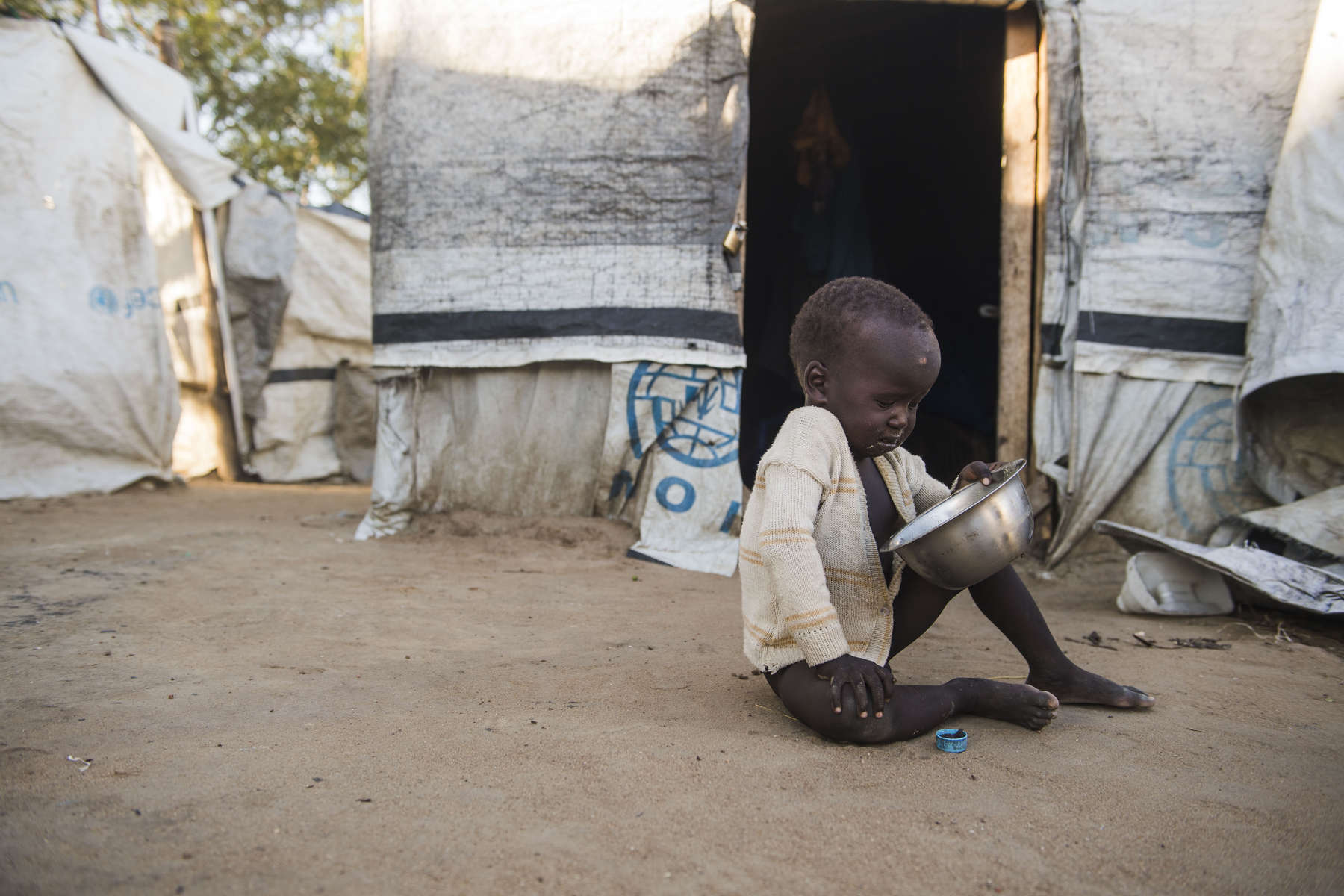 A young boy looks at his empty food bowl, in the Protection of Civilians Site adjacent to the United Nations Mission in South Sudan base in Bor on Tuesday, 31 Oct. in Bor, South Sudan.