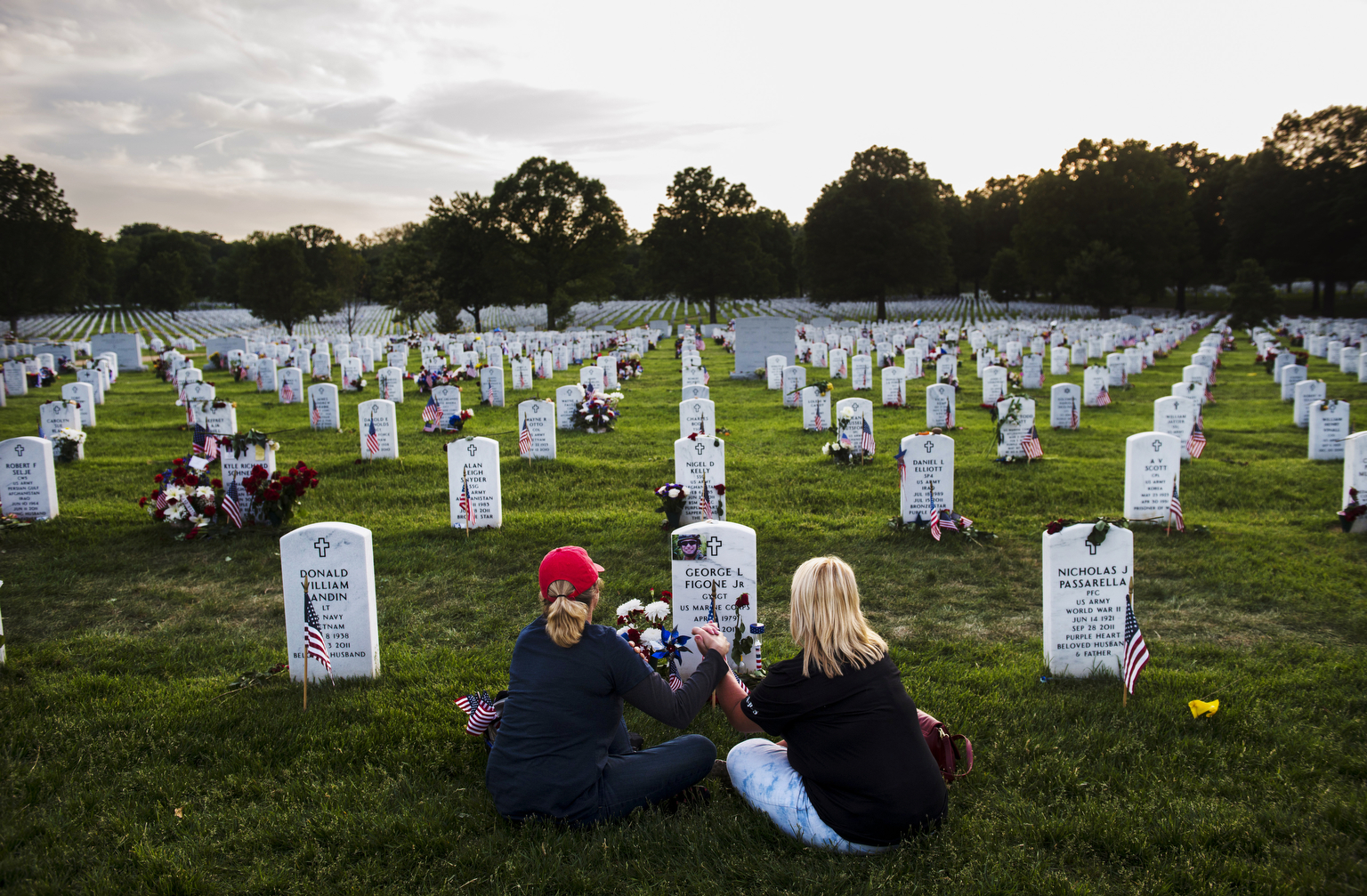 WASHINGTON, DC - MAY 26:  Debbra Figone and her sister, Anne Martin visit the grave site of Figone's son, Gunnery Sgt. George L. Figone Jr. on Memorial Day at Arlington National Cemetery on Monday, May 26, 2014 in Washington, DC. {quote}They called him gorgeous George,{quote} said Figone of her son who died at the age of 32 due to complications after being shot by friendly fire in Afghanistan in 2010.  Figone makes an annual pilgrimage to Arlington from her home in Northern Stockton, CA, visiting for five days over the memorial day weekend as part of the TAPS program. {quote} I come here to be with people that understand.  They don't need something to remind them because we live it every day,{quote} she said. (Photo by Amanda Voisard/For the Washington Post)
