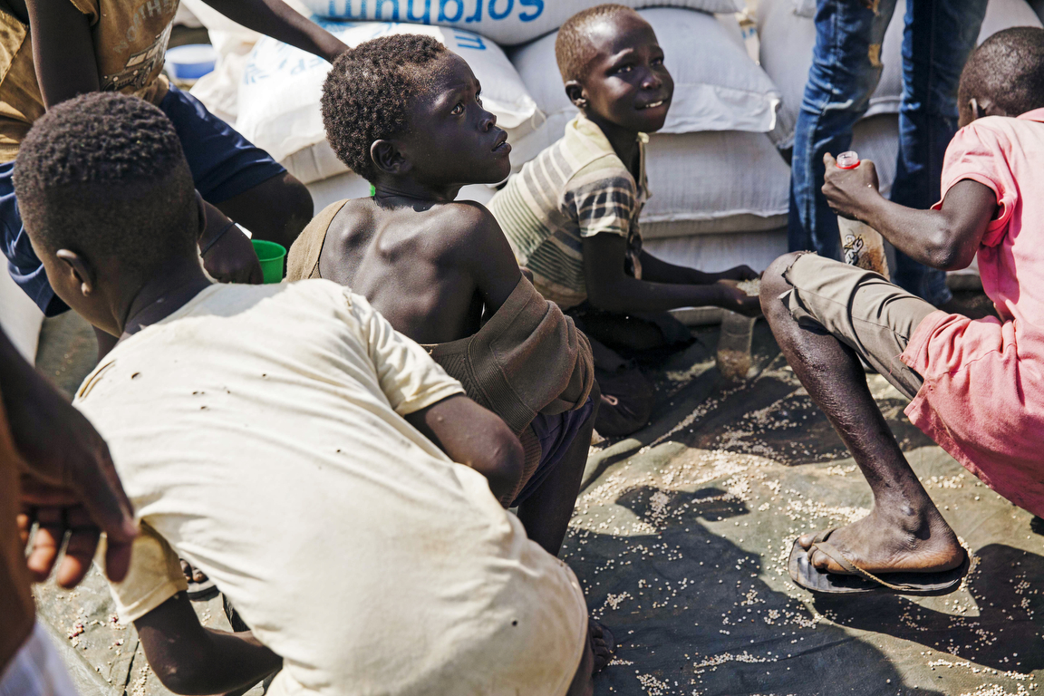 Young boys gather leftover grain at a food distribution site at the Imvepi refugee camp in Northern Uganda as refugees lineup to claim their monthly rations on Saturday, 24 June, 2017.    Record numbers of South Sudanese have fled their home country crossing the border into Uganda, a country now hosting now more than 1.2 million refugees.   Food shortages continue to be an issue in the camp due to the humanitarian response struggling to meet the overwhelming needs of the refugees.