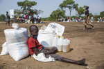 A young man waits with his families monthly rations at a food distribution site at the Imvepi refugee camp in Northern Uganda as on Saturday, 24 June, 2017.  Record numbers of South Sudanese have fled their home country crossing the border into Uganda, a country now hosting now more than 1.2 million refugees.   Food shortages continue to be an issue in the camp due to the humanitarian response struggling to meet the overwhelming needs of the refugees.