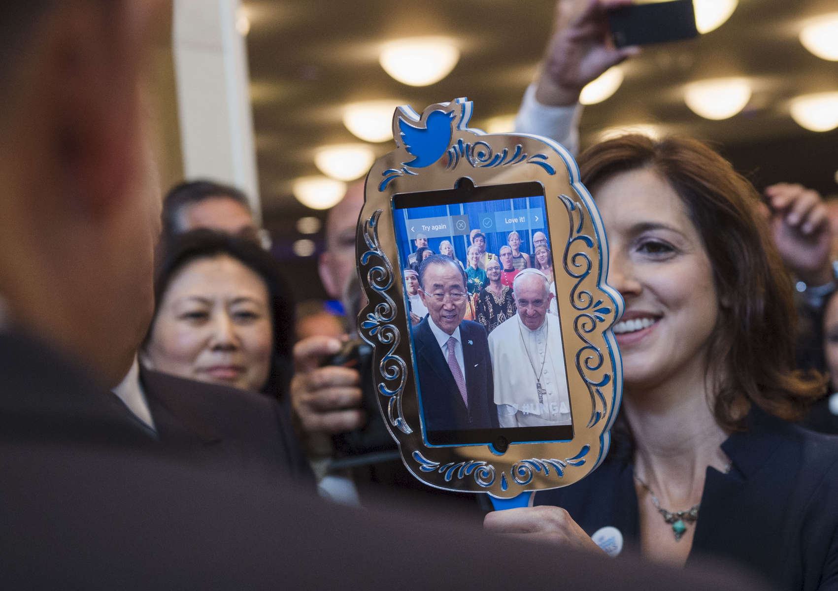 Charlotte Scaddan of the Social Media Team in the UN Department of Public Information (DPI) holds up a Twitter Mirror to Pope Francis and Secretary-General Ban Ki-moon as they stand with the UN Staff Recreation Council Singers performing in the Pope's honour.