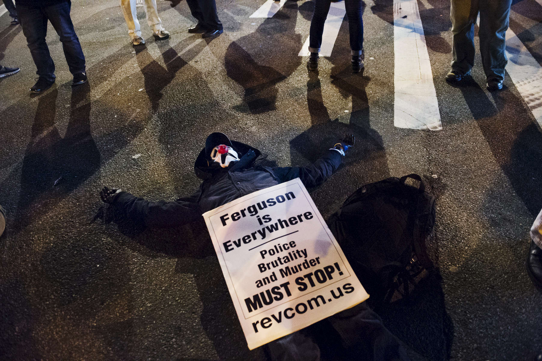 NEW YORK CITY, NY- DEC 4: A masked protestor joins in a die-in at the intersection in front of the Barclays Center in Brooklyn on Dec. 4, 2014 in Brooklyn, NY.   The group of demonstrators took to the streets of New York, a day after a Staten Island grand jury declined to bring charges in the casze of Eric Garner, beginning their march in New York's Foley Square closing down the Brooklyn and Manhattan Bridges as they crossed over.