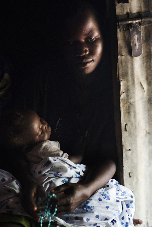 A woman and her daughter seek shelter during a rainstorm in Palaro, Uganda.