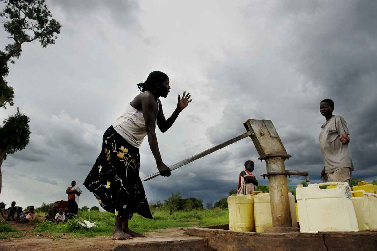 Storm clouds hover overhead as Aderyo Nancy and Aciro Harriett collect water at the local bore hole in Palabek, Uganda.