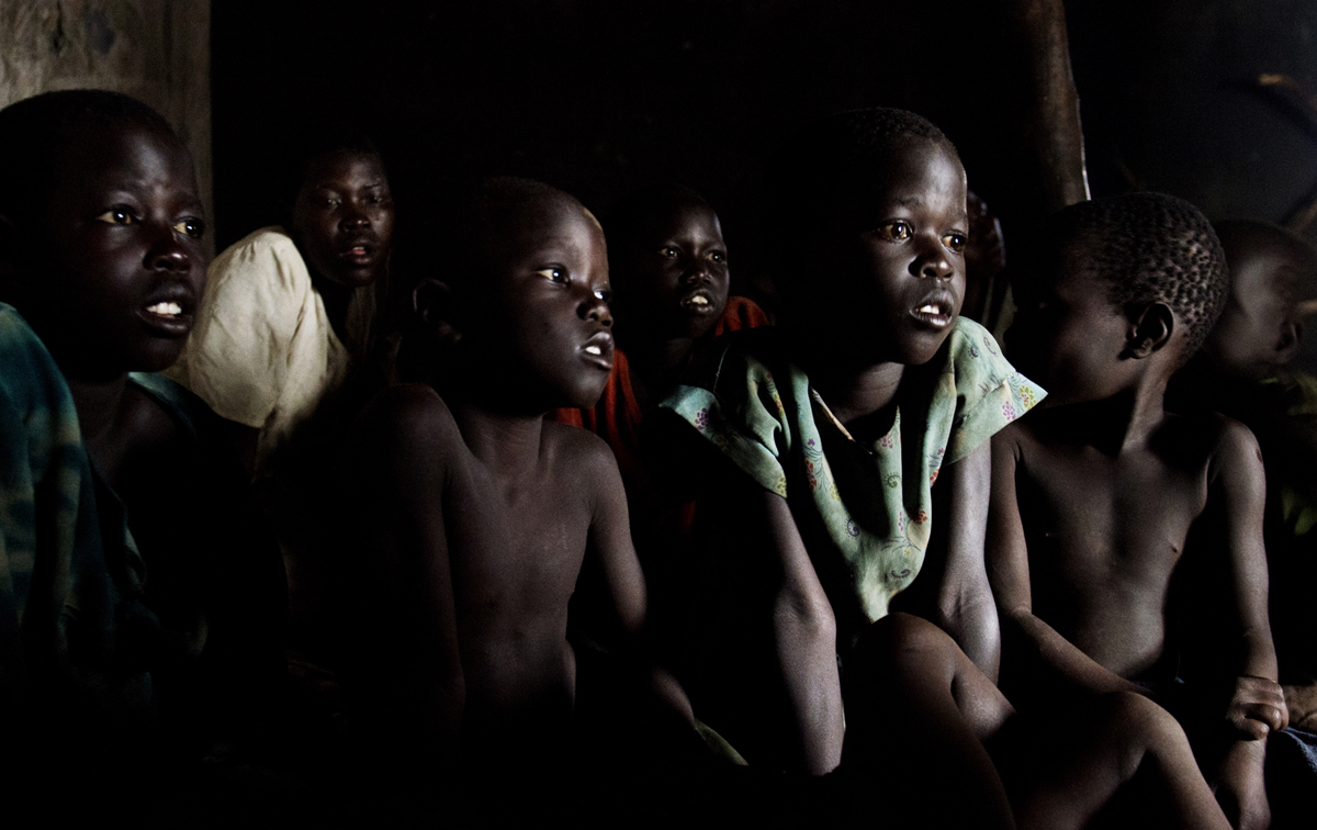 An afternoon thunderstorm forces a group of youngsters inside the kitchen hut of Aciro Harriett in Palabek, Uganda.