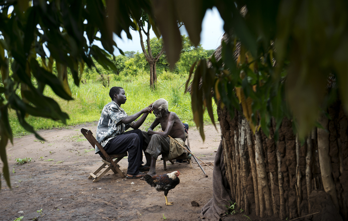 With help from a family member, an Acholi elder gets a haircut.  During the war, many residents of Northern Uganda were forced into overcrowded refuge camps, where some lived for up to twenty years.