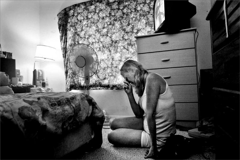 Pam Boyle rests her head in her hands while seated on the floor of the bedroom shared by her daughters, Brianna and Brittany Carleo.