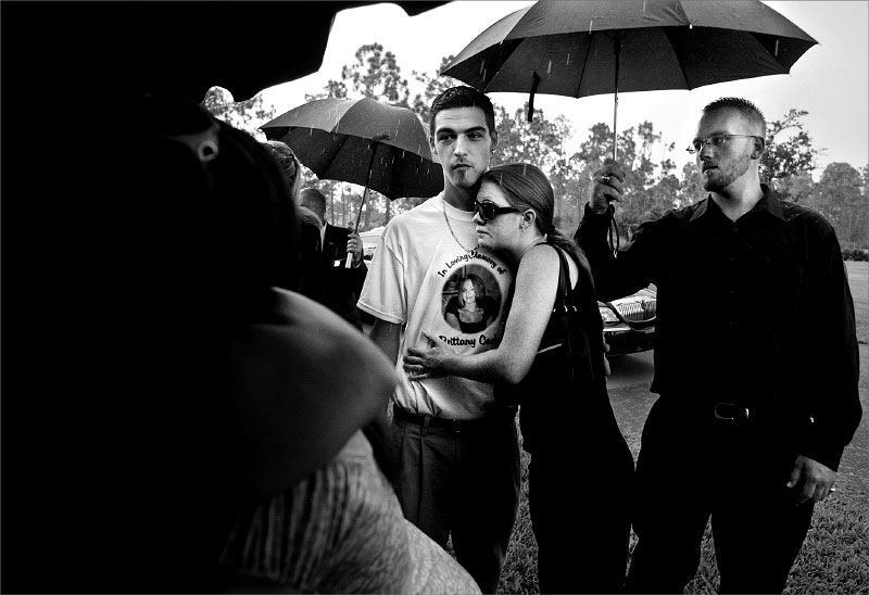 Jeffrey Carleo dressed in a t-shirt comemorating his sister Brittany Carleo stands outside the tent of her burial services with friends, Jennifer Kaeff, middle, and Paul Klinger, right.