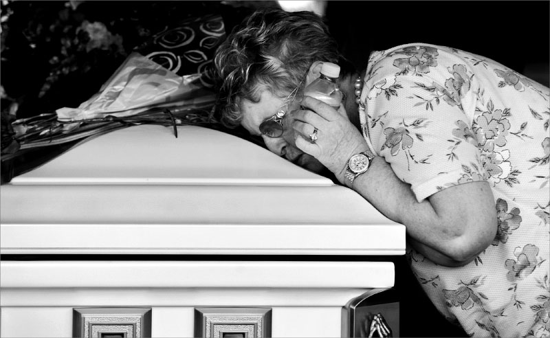 Joyce Boyle lays her head on the coffin of her granddaughter, Brittany Carleo's casket, during burial services at Rolling Oaks Cemetary in Port St. Lucie.