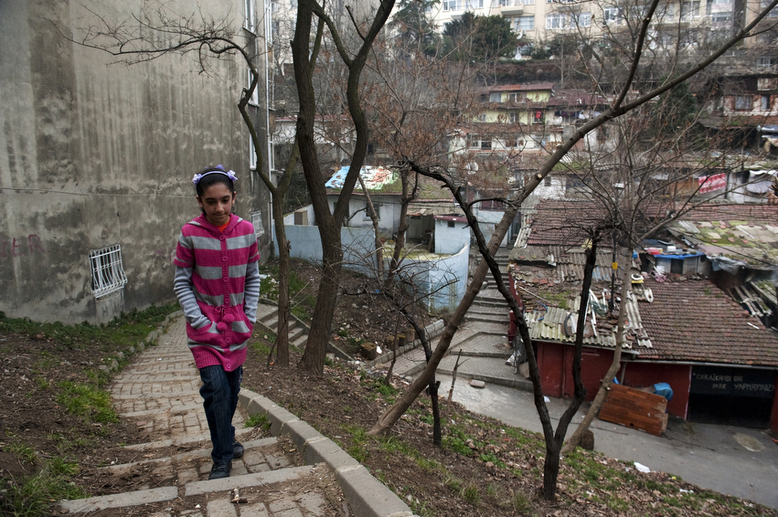 Songul Kesman, 13, walks up the hill from her home to fetch fresh bread for a neighbor.  Songul lives in a the Gecekondu community, a squatter settlement, located in the middle of one of Istanbul's most affluent areas.