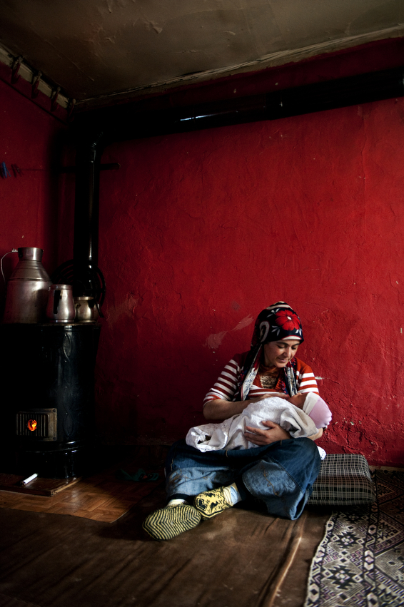 Cidem Kesman nurses her infant-son, Remzi in the one-room home, she, her husband, and five children share in Istanbul, Turkey.   The Kurdish family, moved to Istanbul several years prior and are renting a small Gecekondu or squatter house in the same neighborhood as her in-laws.