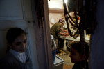 Songul Kesman, 13, and Firat Kesman, 5, wait outside the doorway as their aunt, Gulcan Kesman prepares dinner for the household.