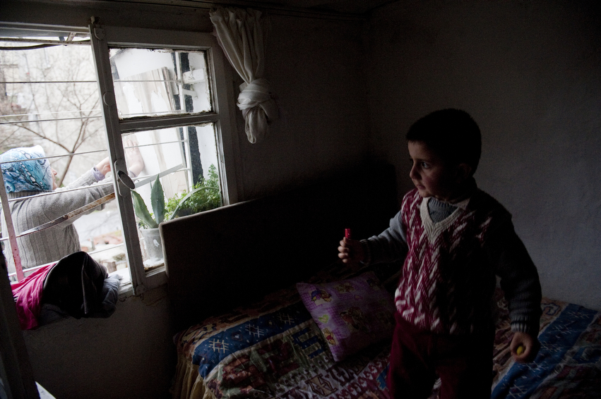 Yusuf Kesman, 4, plays in his parents bedroom as his mother, Gulcan, breaks apart an old door for firewood outside their home.