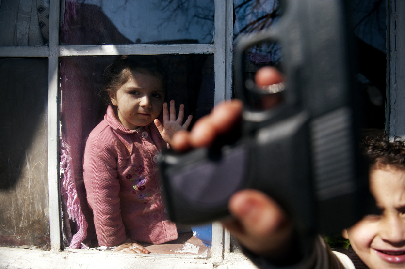 Yarren Kesman, 3, peers out from the window of her Uncle's shanty as her cousin, Firat, 5, takes advantage of the weather outside their home in Istanbul, Turkey.  The family lives within a squatter community of Gecekondu homes, translated as house built over night.  Yarren's father, and two Uncle's work long hours to support the family of 18.