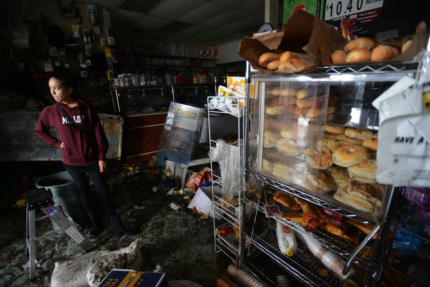 Vanessa Estevez looks over the remains of her families business, Island Park Food Center in Island Park, NY. The business was destroyed when high winds and the storm surge from Hurricane Sandy tore through the shop the night before.
