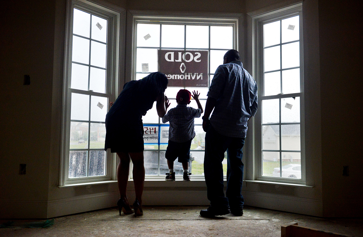 UPPER MARLBORO, MD- JUNE, 28:  Chantal Johnson, holding her youngest son, Kaleb, 5-months,  accompanied by her eldest son, Khalil, 4, and husband Waldo Johnson, left, look out the front window of their new home during a walkthrough on Friday, June 28, 2013 in Upper Marlboro, MD.  The 4-bedroom home, located in Oak Creek, a gated community in Prince George's County, is near completion and will be ready for the family to move-in in the coming months.  (Photo by Amanda Voisard/For The Washington Post)