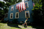 WASHINGTON, DC - JULY 4: Ellie Watkins, 7, runs across her yard past the families oversized Flag following the Palisades Independence Day Parade on July 4, 2013 in Washington, DC. (Photo by Amanda Voisard/For the Washington Post)